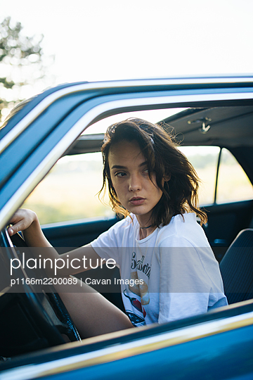 Young woman sitting in a parked vintage car. - p1166m2200089 by Cavan Images