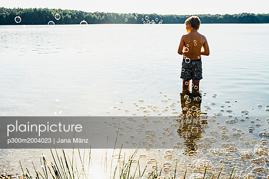 Boy in a lake surrounded by soap bubbles - p300m2004023 von Jana Mänz
