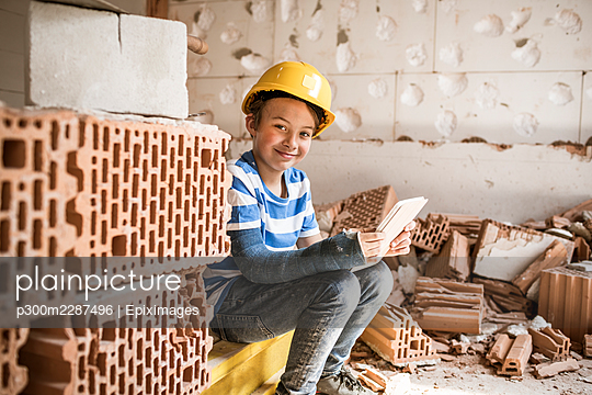 8 year old boy with broken arm on construction site in attic or loft during renovation with digital tablet, austria - p300m2287496 von Epiximages