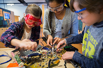 Students in goggles assembling electronic circuit science center - p1192m1019877f by Hero Images