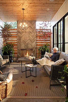 Senior woman relaxing, reading book on living room sofa next to fireplace - p1192m2047668 by Hero Images
