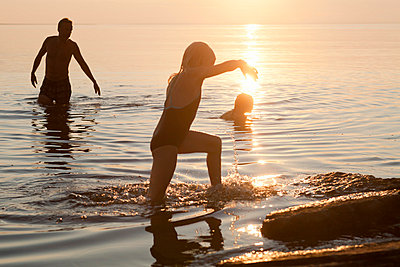 Family playing in lake at sunset - p312m695569 by Ulf Huett Nilsson