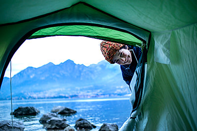 Boy peering into tent by lakeside, Onno, Lombardy, Italy - p429m2069049 by Bonfanti Diego