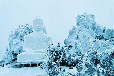 Snow on Buddha statue - p555m1231746 by Aleksander Rubtsov