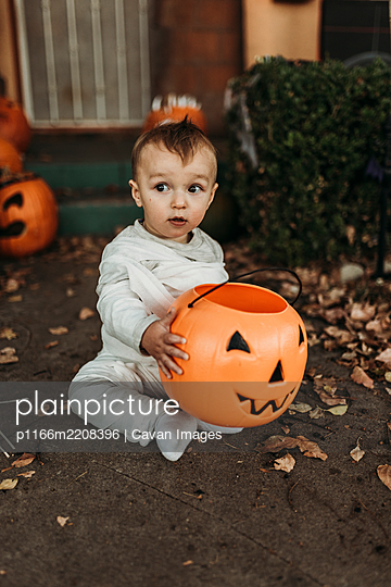 Adorable toddler boy dressed up as mummy on Halloween Trick-or-Treat - p1166m2208396 by Cavan Images