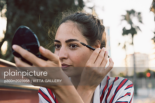 Portrait of woman applying mascara - p300m2023958 von VITTA GALLERY