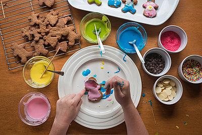 Young girl decorating gingerbread with frosting on a plate - p1166m2137152 by Cavan Images