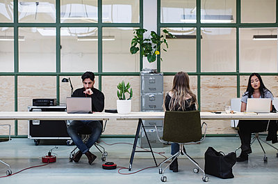 Two women and one man working at desk in creative office - p426m1407194 by Maskot