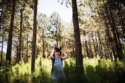 Boy looking through binoculars in woods - p623m1495128 by Eric Audras