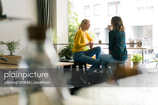 Two girlfriends sitting in coffee shop, drinking coffee - p300m2120834 by Joseffson