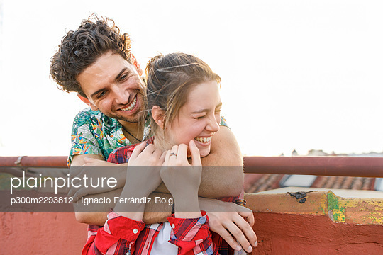 Young man embracing cheerful girlfriend on rooftop during weekend - p300m2293812 by Ignacio Ferrándiz Roig