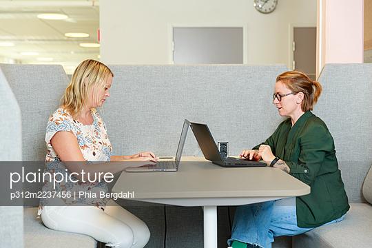 Coworkers using laptops at work - p312m2237456 by Phia Bergdahl