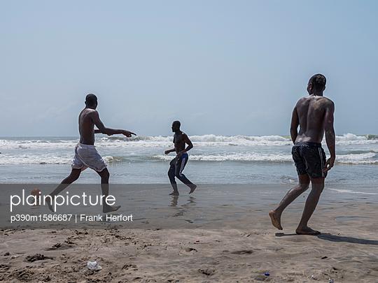 Afrikaner spielen Fussball am Strand - p390m1586687 von Frank Herfort