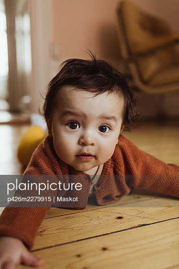 Portrait of baby boy lying on floor at home - p426m2279915 by Maskot