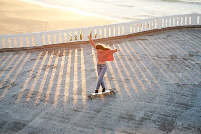 Female longboarder on boardwalk at sunset  - p1124m1503658 by Willing-Holtz