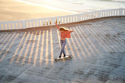 Junge Frau auf einem Longboard bei Sonnenuntergang - p1124m1503658 von Willing-Holtz