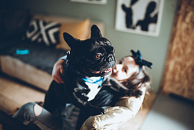 High angle view of girl with French Bulldog sitting sofa at home - p1166m1474262 by Cavan Images