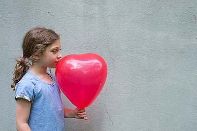 Side view of girl looking away while holding balloon against wall - p1166m1486029 by Cavan Images