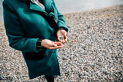Detail of the hands of a woman showing some stones by the sea - p1166m2078402 by Cavan Images