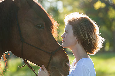 Profiles of young woman and horse at backlight - p300m1459933 by Tom Chance