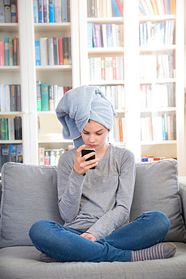Girl wearing towel turban sitting on couch at home looking at cell phone - p300m1580705 von Larissa Veronesi