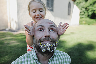 Portrait of mature man with daisies in his beard playing with little daughter in the garden - p300m2029552 by Katharina Mikhrin
