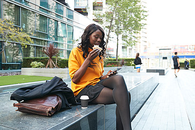 Businesswoman having sandwich while using mobile phone at office park - p300m2241594 by Pete Muller