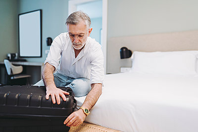 Man closing suitcase while sitting on bed in hotel room - p300m2250684 by Daniel González
