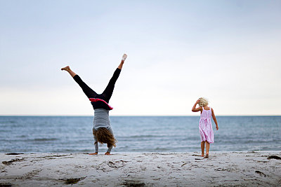 Two girls playing on a beach by the sea Sweden - p31223750f by Ulf Huett Nilsson