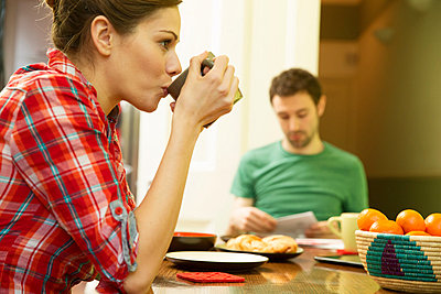 Young couple at breakfast, woman drinking coffee - p429m801622 by Igor Emmerich