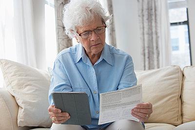 Older Caucasian woman using digital tablet to pay bills - p555m1311736 by Jose Luis Pelaez Inc.