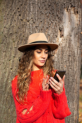 Young woman in red jumper sending text messsage - p975m2222118 by Hayden Verry
