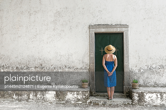 Woman with straw hat in front of a church - p1445m2124871 by Eugenia Kyriakopoulou