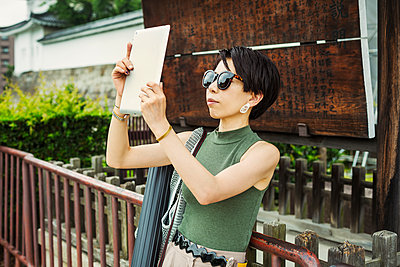 A woman using a tablet to take a photograph at a historic temple.  - p1100m1185887 by Mint Images