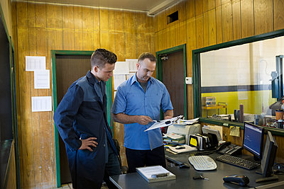 Mechanics reviewing paperwork auto shop office - p1192m1128068f by Hero Images
