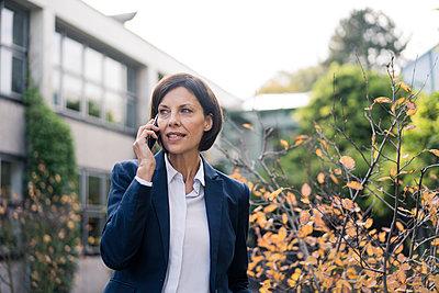 Mature businesswoman talking on smart phone at office park - p300m2266632 by Joseffson
