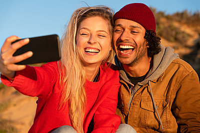 Happy couple smiling while taking selfie through mobile phone sitting outdoors - p300m2267259 by Steve Brookland