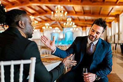 Male friends greeting while sitting and holding champagne at banquet - p300m2274260 by Ezequiel Giménez