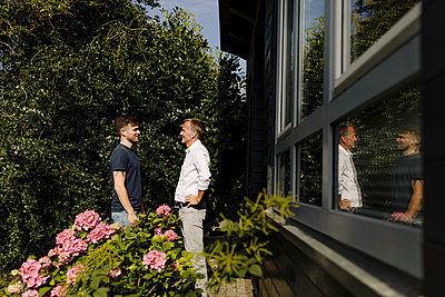 Son and father talking while standing at backyard - p300m2275104 by Gustafsson