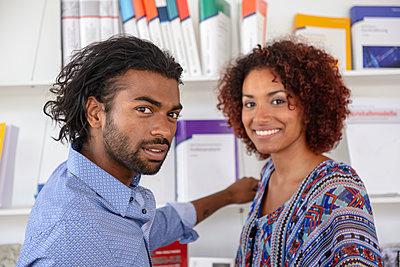 Businessman with female colleague near bookshelf at office - p300m2281528 by Buero Monaco