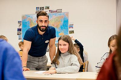 Teacher with schoolgirl in classroom - p312m2174780 by Scandinav