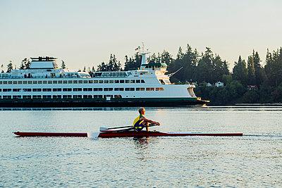 Caucasian man rowing on lake near cruise ship - p555m1303399 by Pete Saloutos