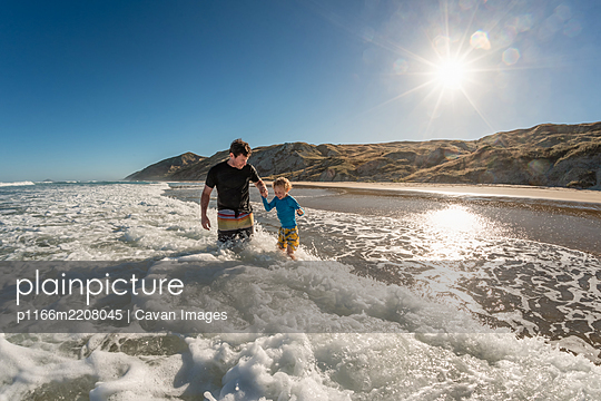 Smiling father and child playing in waves on a sunny day at a beach in New Zealand - p1166m2208045 by Cavan Images