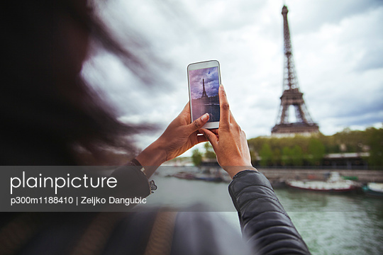 France, Paris, Young woman taking smart phone picture of the Eiffel Tower - p300m1188410 by Zeljko Dangubic