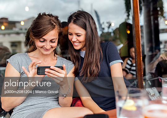 Two women having fun with their smartphone on a terrace - p300m2081204 by Marco Govel