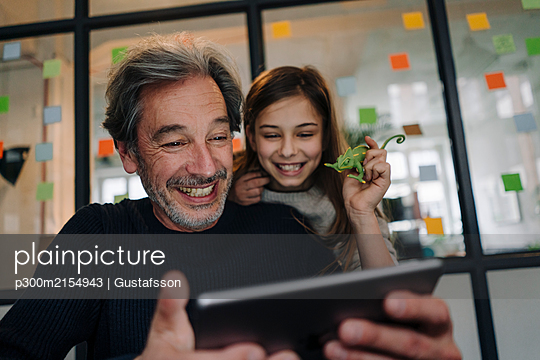 Happy casual senior buisinessman and girl using tablet in office - p300m2154943 by Gustafsson