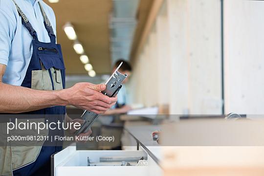 Craftsman holding piece of metal - p300m981231f by Florian Küttler (Coop)