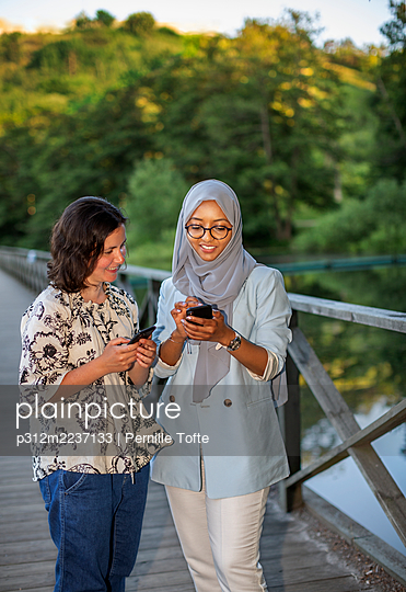 Female friends checking cell phone - p312m2237133 by Pernille Tofte