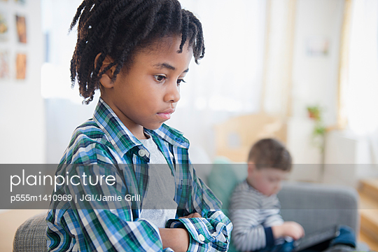 Boy ignoring friend in living room