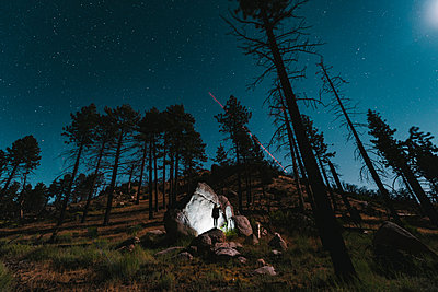 Hiker standing by illuminated rocks amidst trees on field against sky at night - p1166m1183044 by Cavan Images